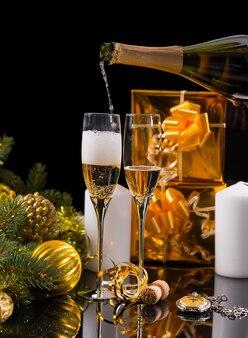 お祝いの静物-白いキャンドル、ゴールドで包まれたギフト、クリスマスボールと見掛け倒しで飾られた常緑樹の黒い背景の前にグラスにシャンパンを注ぐ