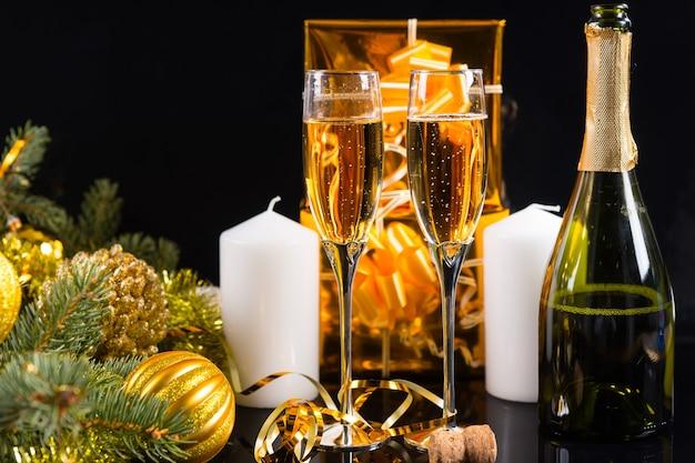 お祝いの静物-ボトル、白いキャンドル、ゴールドラップギフト、クリスマスボールで飾られた常緑樹と黒の背景にスパークリングシャンパン2杯