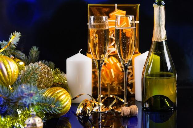 お祝いの静物-黒い背景にボトル、キャンドル、ギフト、クリスマスの装飾が施されたスパークリングシャンパン2杯 Premium写真