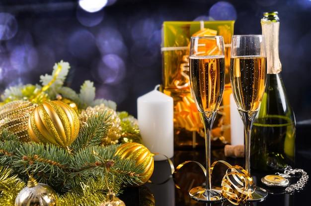 お祝いの静物-黒い背景にボトル、キャンドル、ギフト、クリスマスの装飾が施されたスパークリングシャンパン2杯