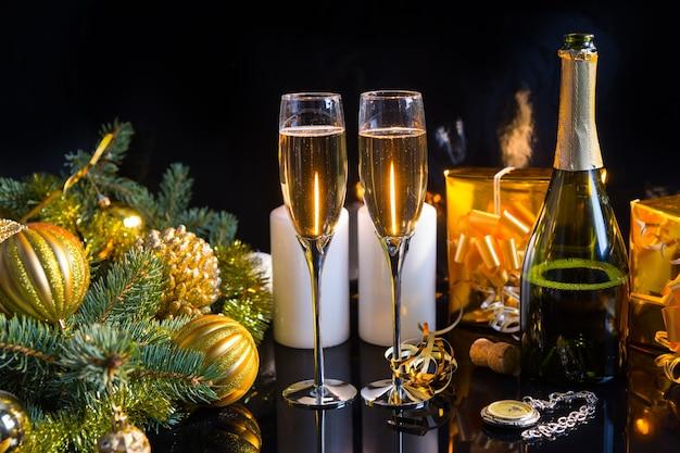 お祝いの静物-ボトル、キャンドル、ギフト、懐中時計、黒い背景にクリスマスの装飾が施されたスパークリングシャンパン2杯