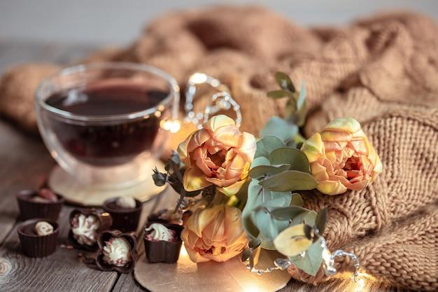 Праздничный натюрморт с напитком в чашке, шоколадом и цветами на размытом фоне.
