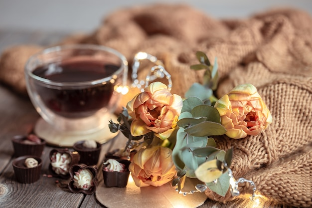 Festive still life with a drink in a cup, chocolates and flowers on a blurred background.