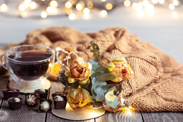 Festive still life with a drink in a cup, chocolates and flowers on a blurred table with bokeh.