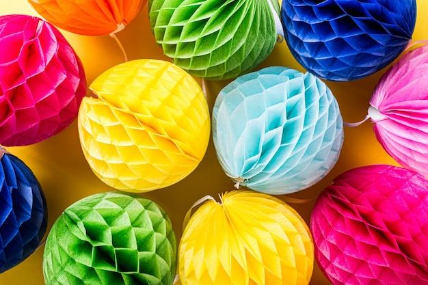 Праздничная поверхность с красочными бумажными шарами. концепция поздравительной открытки для дня рождения, вечеринки, приглашения, карнавала. вид сверху, плоская планировка