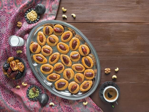 茶色の木製のテーブルに自家製の日付クッキーとお祝いの甘いラマダンテーブル