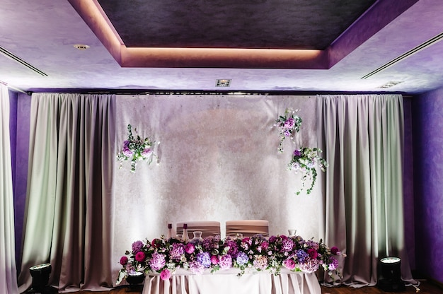 Festive table, arch decorated with composition of violet, purple, pink flowers and greenery in the banquet hall. table newlyweds in the area on wedding party.