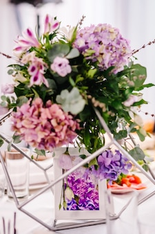 Festive table decorated with composition of violet, purple, pink flowers and greenery in the banquet hall. table newlyweds in the area on wedding party.