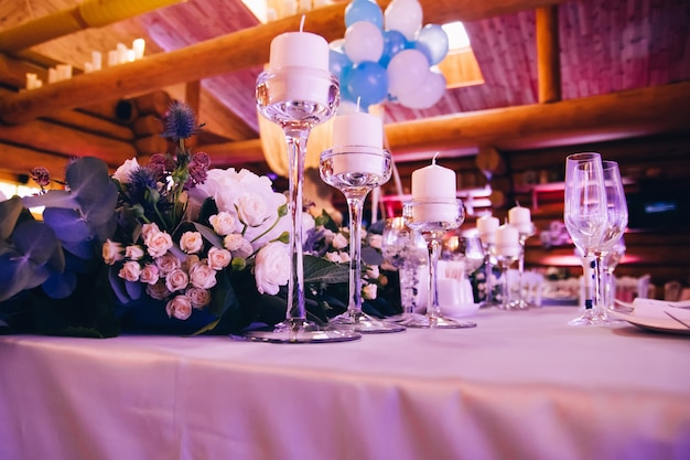 Festive table decorated with garland of branches and flowers, candles on the center.