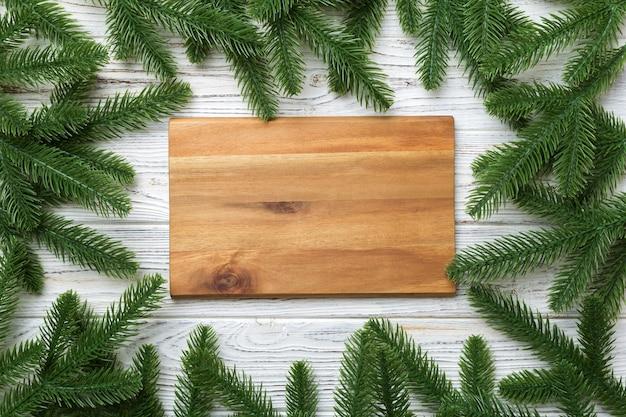 Украшение праздничного стола новогодними ветвями и пустой тарелкой. вид сверху с пространством для текста. рождественское время