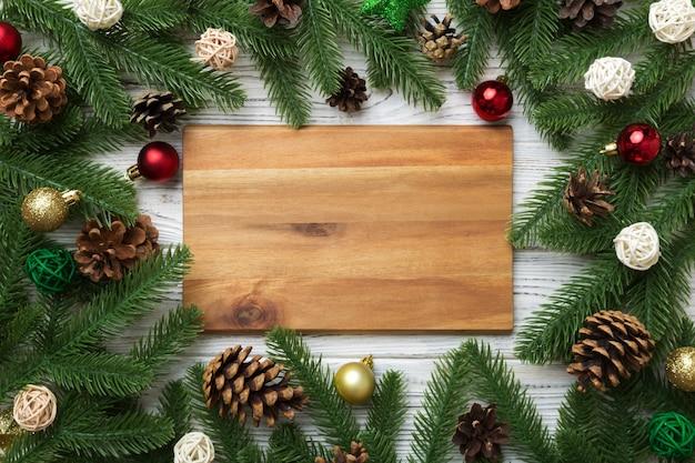 Украшение праздничного стола новогодними ветками и декором пустой тарелки. вид сверху с пространством для текста. рождественское время.