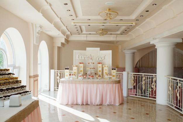 Праздничный стол для жениха и невесты украшен тканью и цветами. свежий цветочный
