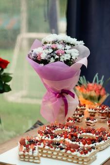 케이크와 아름다운 꽃 부케가있는 18 번째 생일 축제 테이블