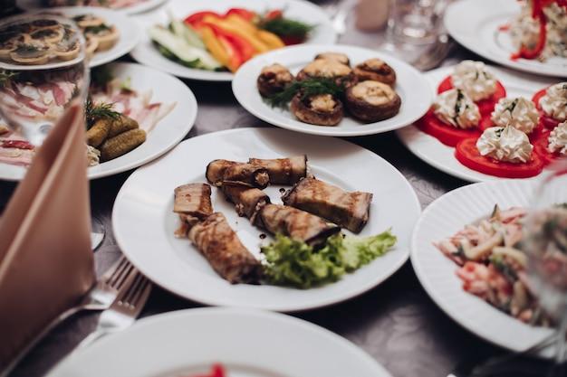Праздничный стол, полный различных холодных закусок