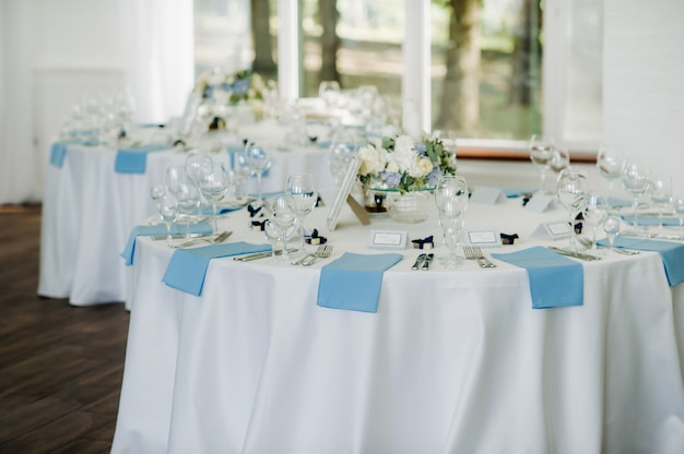 The festive table is decorated in light colors with blue napkins and flowers without food.