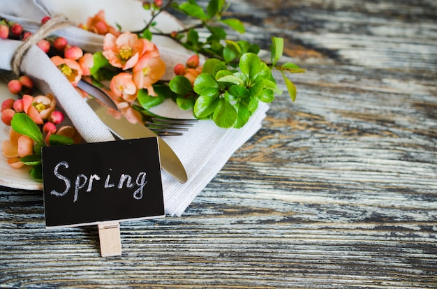 Festive table place setting with spring blossoming branch on wooden background.