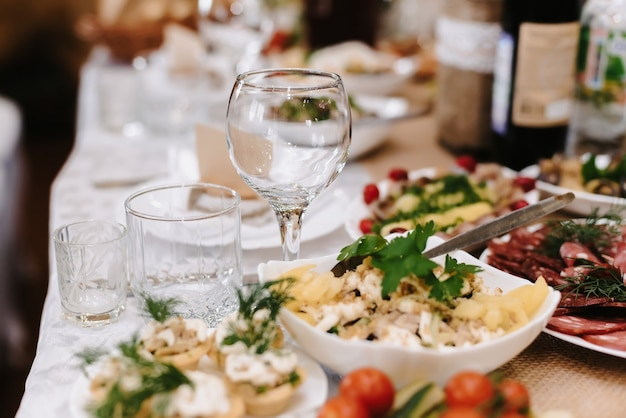 Festive table in the restaurant with wine glasses and various food