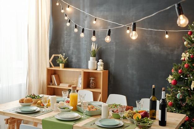 Праздничный стол для рождественской вечеринки с лампами, висящими над едой, и украшенной елкой у черной стены