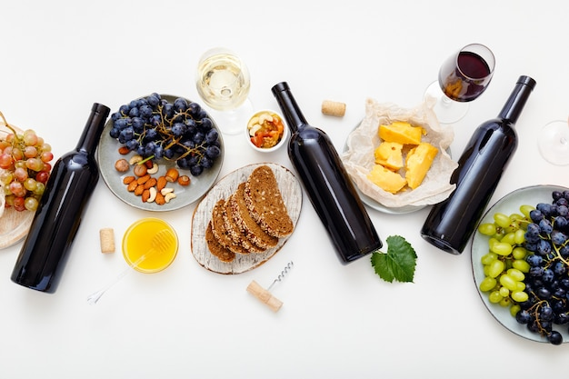 Festive table served with red wine and mediterranean food appetizer snack on white background. wine party event dinner table with set cheese grapes honey nuts. flat lay banner.