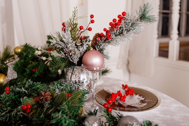 Festive table setting among winter decorations and white candles. top view, flat lay. the concept of a christmas or thanksgiving family dinner.