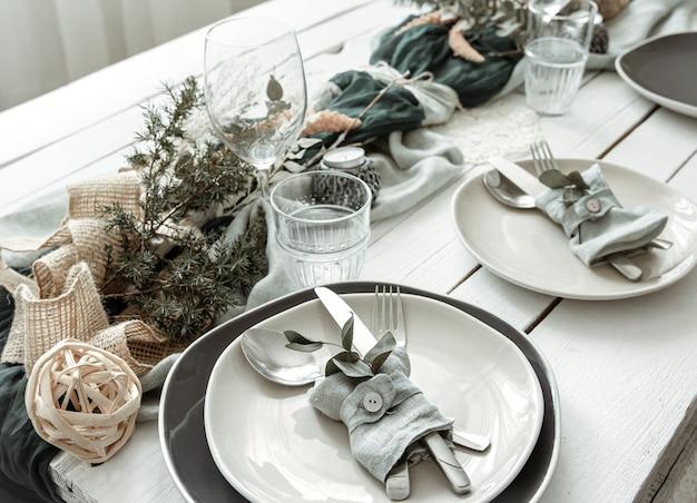 Сервировка праздничного стола дома со скандинавскими декоративными деталями крупным планом