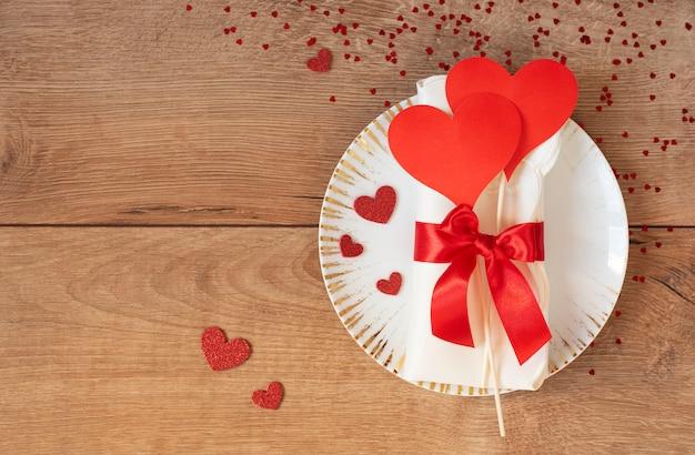 Праздничная сервировка на день святого валентина. золотые тарелки с сердечками и красный бант на деревянном столе. пространство для текста. вид сверху
