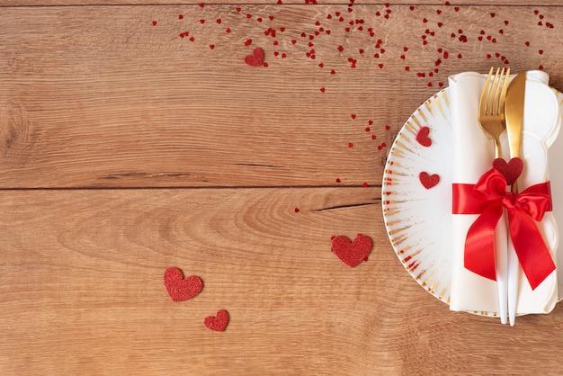 Праздничная сервировка на день святого валентина с вилкой, ножом, красным бантом и сердца на деревянном столе. пространство для текста. вид сверху