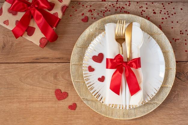 Праздничная сервировка на день святого валентина с вилкой, ножом, красным бантом, подарком и сердца на деревянном столе. пространство для текста. вид сверху