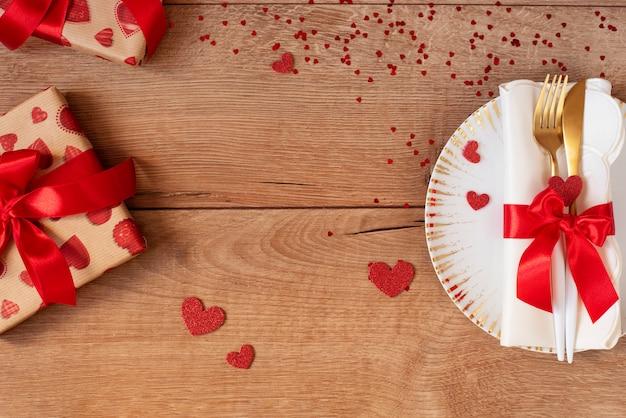 Праздничная сервировка на день святого валентина с вилкой, ножом, красный лук, подарки и сердца на деревянном столе. пространство для текста. вид сверху