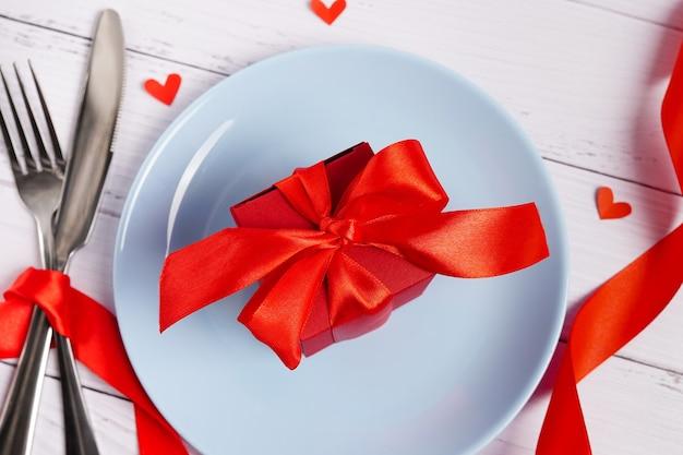 Сервировка праздничного стола на день святого валентина с красной подарочной коробкой, вилкой, ножом и сердечками