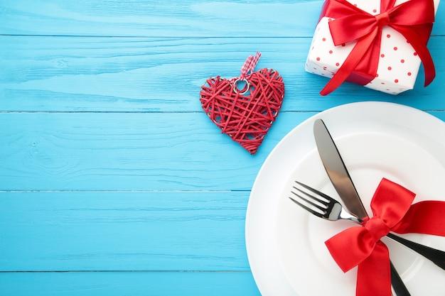 Сервировка праздничного стола на день святого валентина на синем деревянном