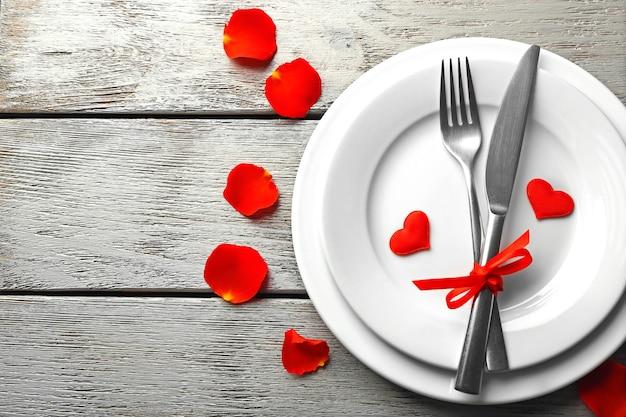 木製テーブルのバレンタインデーのためのお祝いのテーブルセッティング
