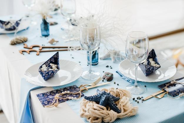 Праздничная сервировка в морском стиле. элегантные тарелки, бумажные стаканчики, соломинки, синий текстиль. бумажные кораблики с зефиром. день рождения или концепция детского душа мальчика.