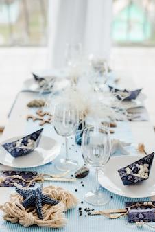 Праздничная сервировка в морском стиле. старинные тарелки, бумажные стаканчики, соломинки и столовые приборы с синим и желтым текстилем. бумажные кораблики со сладостями. день рождения или мальчик, детский душ.