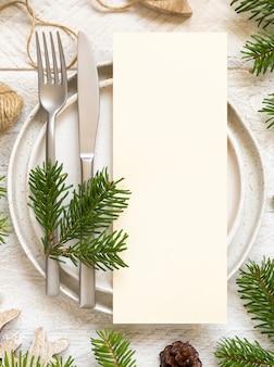 Сервировка праздничного стола из тарелок, столовых приборов и вид сверху ветвей ели. макет рождественского или новогоднего меню на белом деревянном столе, копией пространства. зимняя свадьба, ресторан праздничный кейтеринг