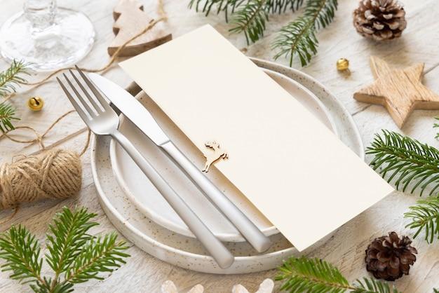 Сервировка праздничного стола из тарелок, столовых приборов и еловых веток с макетом рождественского или новогоднего меню на белом деревянном столе, копией пространства. зимняя свадьба, ресторан праздничный кейтеринг