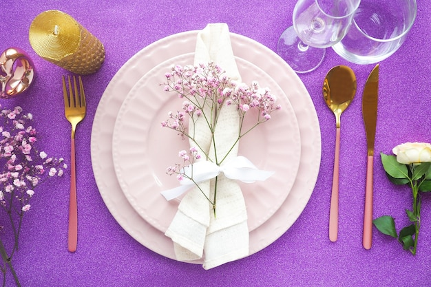 光沢のある紫色のテーブルに2つのピンクのプレートのお祝いのテーブルセッティング