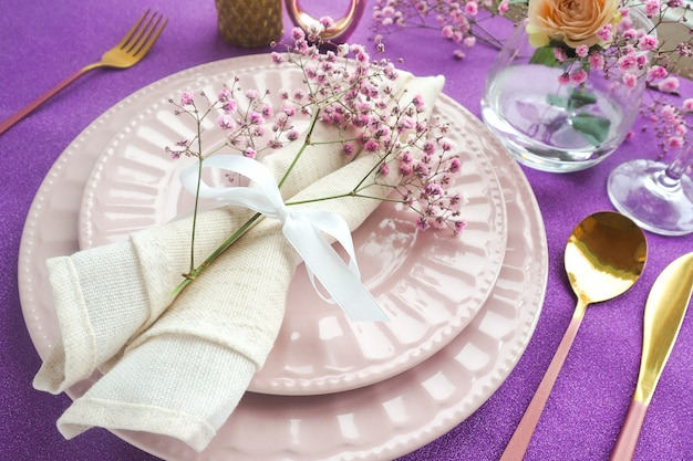 Сервировка праздничного стола на блестящий фиолетовый стол двумя розовыми тарелками