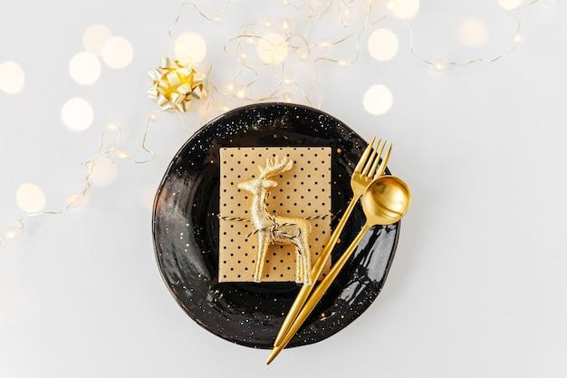 축제 테이블 세팅. 접시, 흰색 바탕에 선물이 있는 황금 칼 붙이. 아름다운 평면 배치.