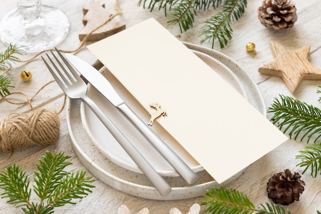 Festive table setting of plates, cutlery and fir tree branches with mockup of christmas or new year menu on white wooden table, copy space. winter wedding, restaurant holiday catering