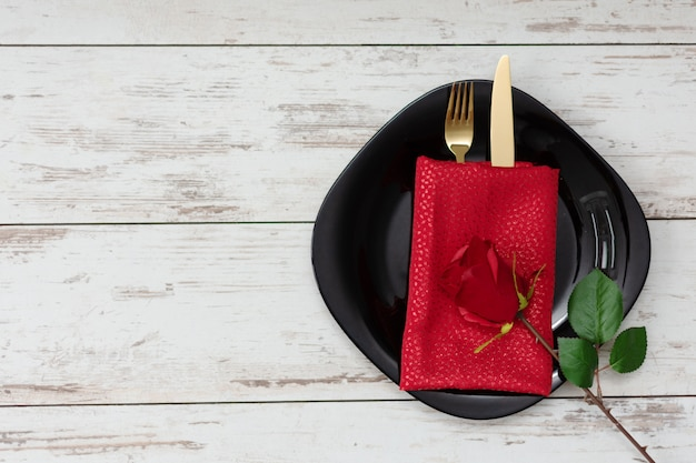 Festive table setting for valentine's day with golden fork and knife and decorations.