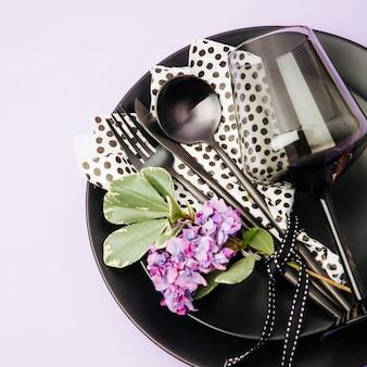 パステルカラーの背景に黒のカトラリー、ナプキン、プレート、ワイングラスとお祝いのテーブルセッティング