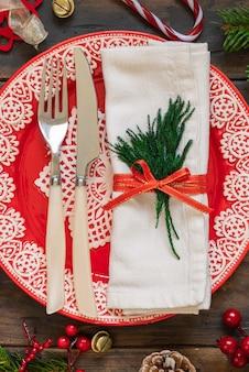 Сервировка праздничного стола с еловыми ветками и елочными украшениями