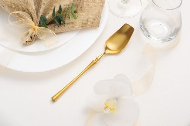 Сервировка праздничного стола золотыми столовыми приборами, бежевая салфетка, зеленая веточка, белые цветы на легкой скатерти