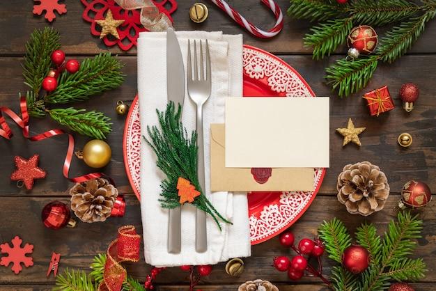 休日の装飾モミの木の枝の空白のカードと封筒とお祝いのテーブルの設定