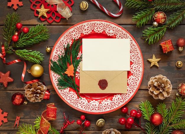 Сервировка праздничного стола с праздничными украшениями еловые ветки пустая карточка и конверт