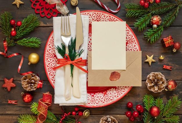 休日の装飾モミの木の枝の空白のカードと封印された封筒とお祝いのテーブルの設定