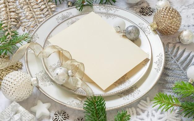 Сервировка праздничного стола с украшениями и еловыми ветками. макет пригласительного билета на рождество или новый год на белом мраморном столе, копией пространства. зимний сезон, ресторан праздничное питание