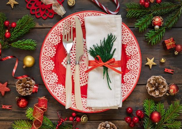 Сервировка праздничного стола с украшениями и ветвями ели на вид сверху деревянного стола. рождественские или новогодние плоские планировки. зимний сезон, ресторан праздничное питание