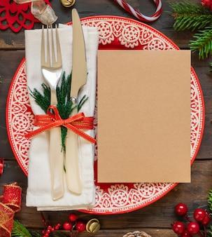장식 전나무 나뭇가지와 빈 카드 상단 보기가 있는 축제 테이블 설정